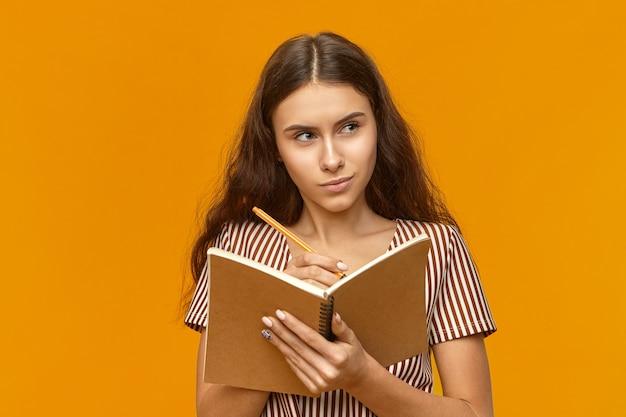 Wunderschönes studentenmädchen im gestreiften kleid, das tagebuch und stift hält