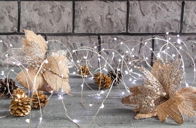 Wunderschönes weihnachtsdekor in silbrigen goldtönen goldene tannenzapfen weihnachtslichter und blume auf einem k...