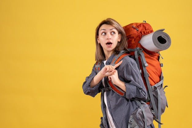 Wunderte reisende frau mit rotem rucksack
