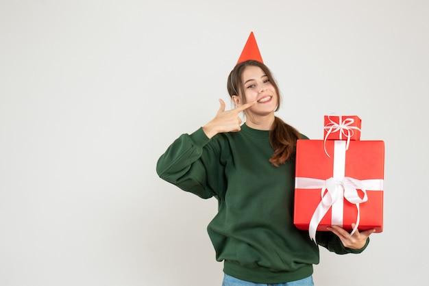 Wunderte sich mädchen mit partykappe, die geschenke hält, die auf ihr lächeln auf weiß zeigen