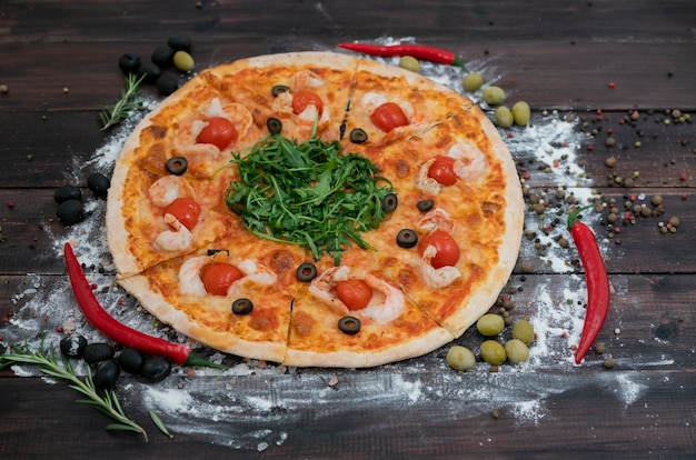 Wundervolle und geschmackvolle italienische pizza liegt auf einem dunklen hintergrund von den hölzernen brettern.