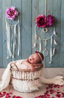 Wundervolles kind, das träumerisch im korb schläft