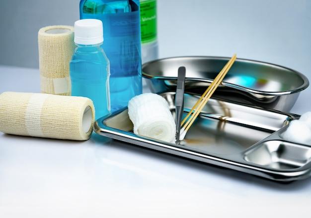 Wundversorgungsset und edelstahlplatte, pinzette, jodbecher, konformer verband, elastischer kohäsiver retentionsverband, antiseptische und normale kochsalzlösung.