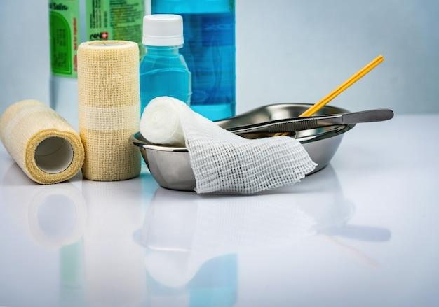 Wundversorgungsverband und edelstahlbecken, pinzette, alkoholflasche, normale kochsalzlösung, kohäsiver elastischer verband, passender verband, behälter für chirurgische eingriffe.