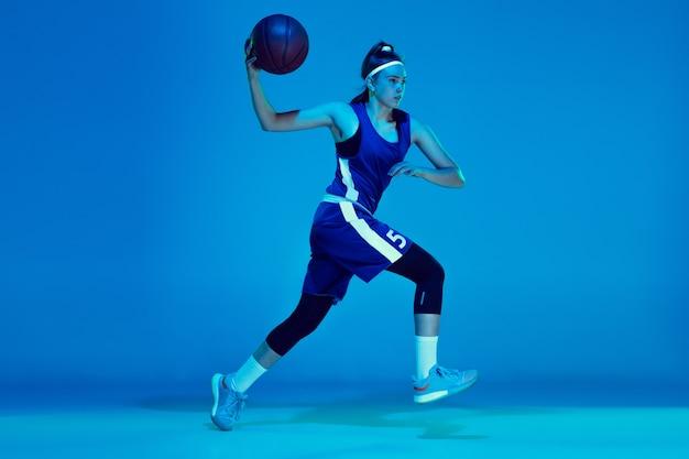 Wunsch zu gewinnen. junge kaukasische basketballspielerin training, prcticing mit ball auf blauem hintergrund im neonlicht isoliert. konzept von sport, bewegung, energie und dynamischem, gesundem lebensstil.