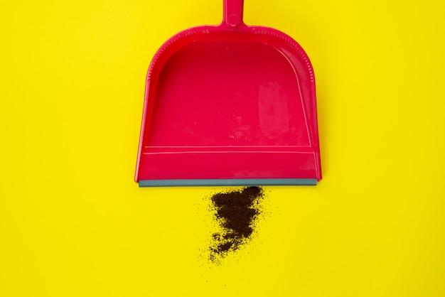 Wurf vom boden fegen. fegt kaffee in eine rote kugel auf einem gelben tisch. einfache reinigung
