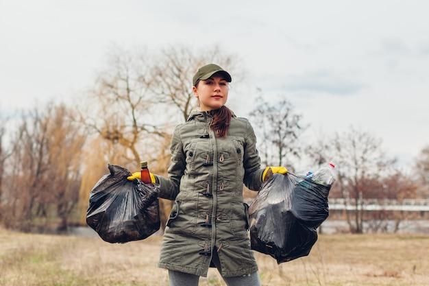 Wurfsammeln. freiwillige frau, die den abfall im park aufräumt. müll draußen aufheben. ökologie und umwelt