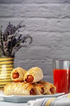 Wurst im teig auf einer platte mit tomatensaft