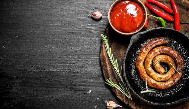 Wurst in einer pfanne mit heißer tomatensauce an der schwarzen tafel