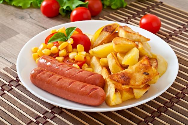 Wurst mit bratkartoffeln und gemüse auf einem teller