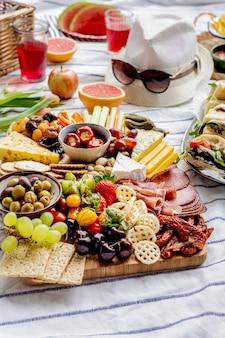 Wurstbrett mit aufschnitt, frischem obst und käse, sommerpicknick