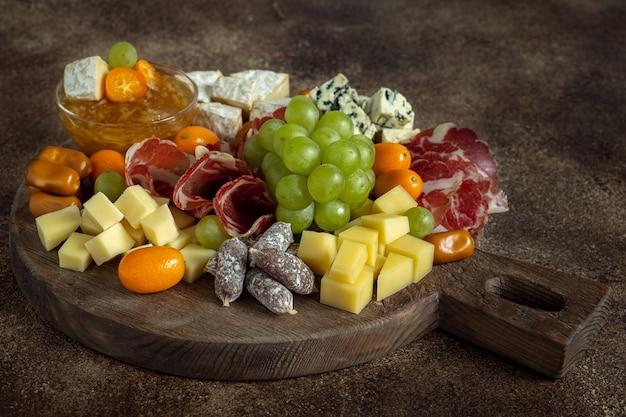 Wurstbrett mit verschiedenen käsesorten, trauben, kumquat und ingwermarmelade auf holztisch