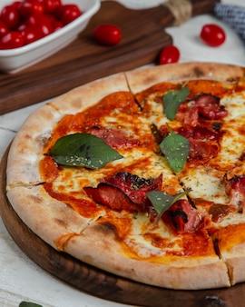 Wurstpizza garniert mit lorbeerblatt