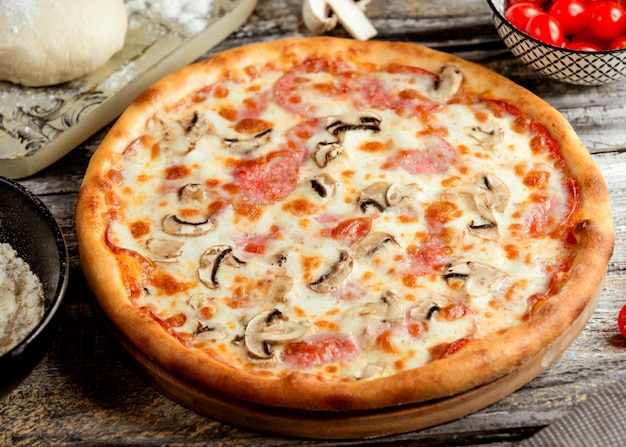 Wurstpizza mit pilzen auf dem tisch