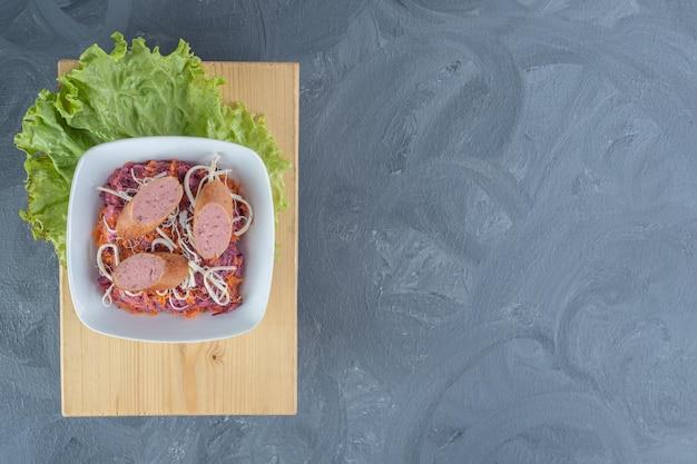 Wurstscheiben, geriebener käse und ein salatblatt schmücken eine schüssel walnuss-rüben-salat auf marmortisch.