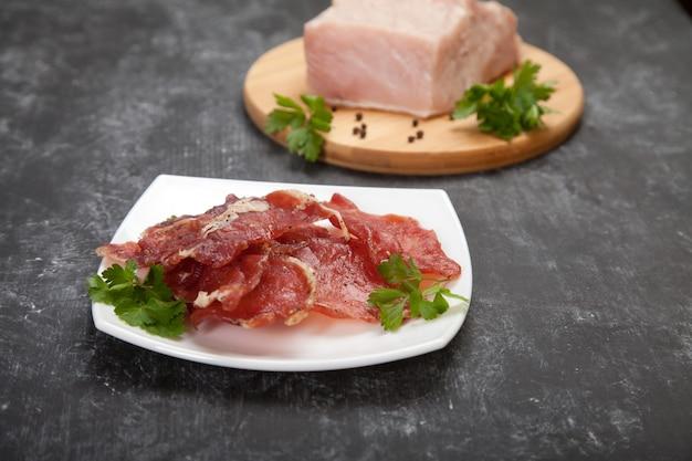 Wurstwaren auf einem weißen teller und rohes fleisch mit kräutern auf einem holzbrett auf schwarzem hintergrund.