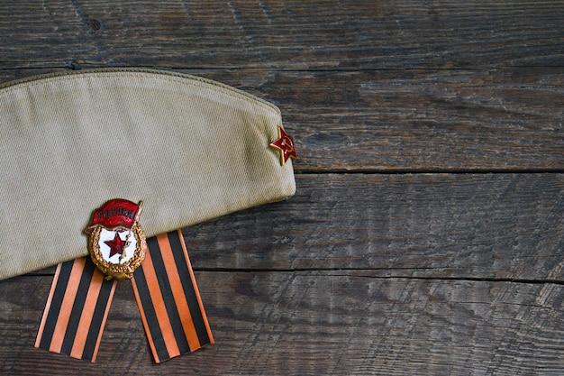 Wwii soldatenmütze und gardemedaille auf holzuntergrund