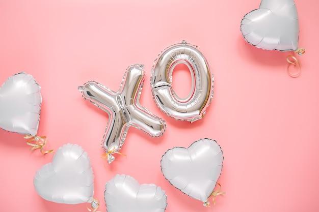 Xo folienballon und luftballons in herzform. liebe konzept. urlaub und feier. valentinstag oder hochzeits-/junggesellinnenabschiedsdekoration. silberne metallische luftballons auf rosa hintergrund.