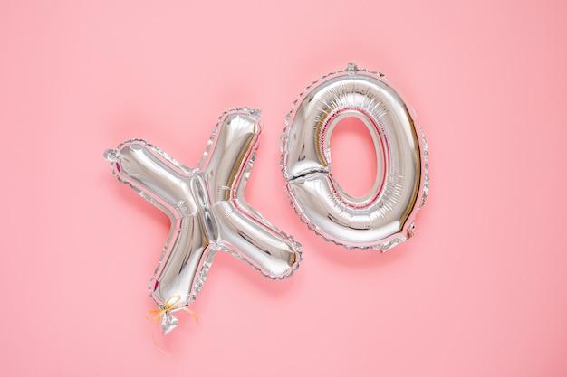Xo folienballonbuchstaben. liebe konzept. urlaub und feier. valentinstag oder hochzeits-/junggesellinnenabschiedsdekoration. silberne metallische luftballons auf rosa hintergrund.