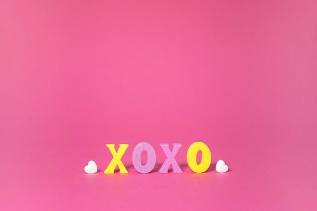 Xoxo wort mit weißem herzen auf rosa