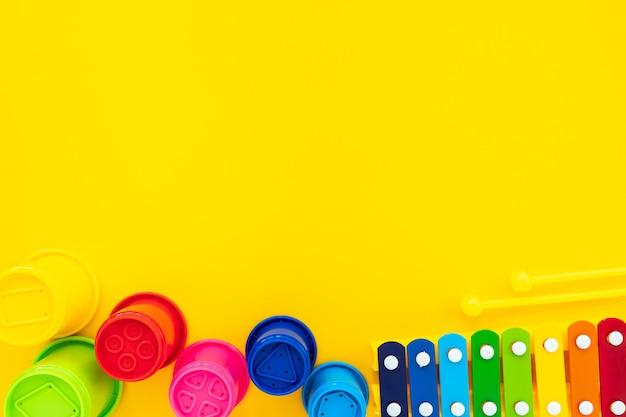 Xylophon und pyramide der hellen regenbogenkinder auf gelbem grund. komposition mit kinderspielzeug, draufsicht, flachlage, kopierraum.