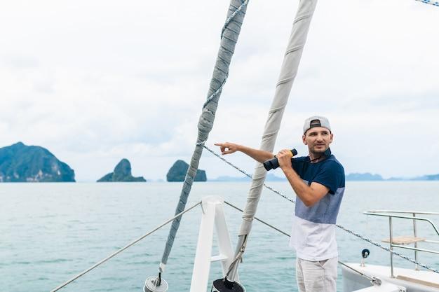 Yacht des jungen mannes, die durch ferngläser schaut. reisen und aktives leben.