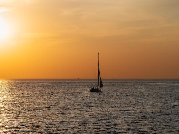 Yacht in ruhe bei sonnenuntergang minimalistische seelandschaft