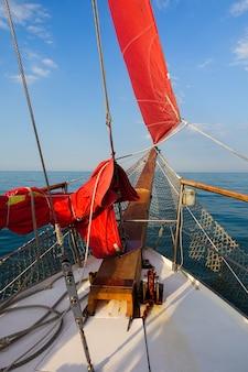 Yacht mit roten segeln im offenen meer.