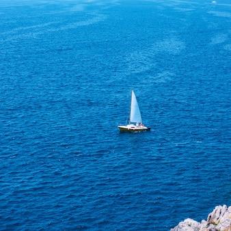 Yacht mit segeln im meer in der nähe der küste am sommertag - minimalistische meereslandschaft