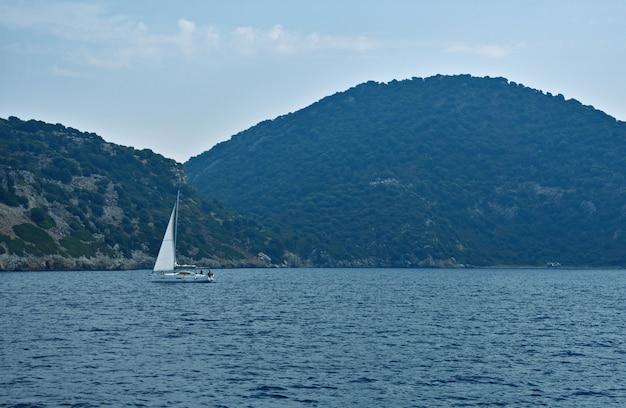 Yacht segelt auf dem meer entlang der berge