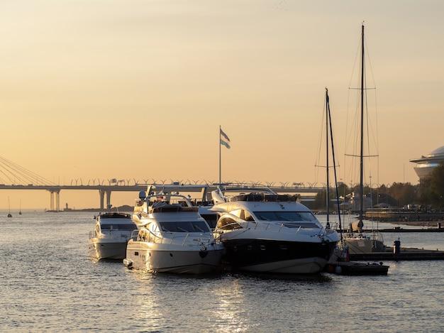 Yachten auf dem pier bei sonnenuntergang newa fluss, sankt petersburg