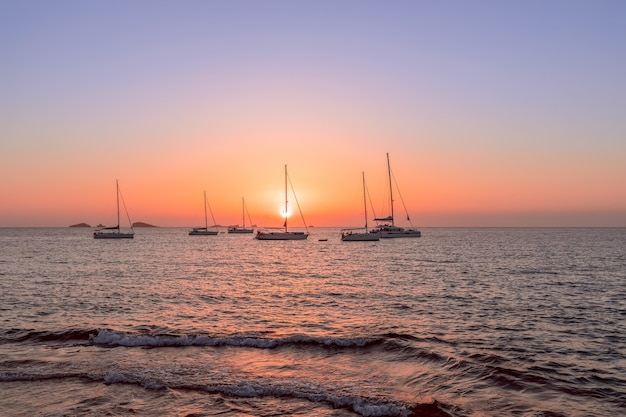 Yachten auf see während des atemberaubenden sonnenuntergangs in ibiza