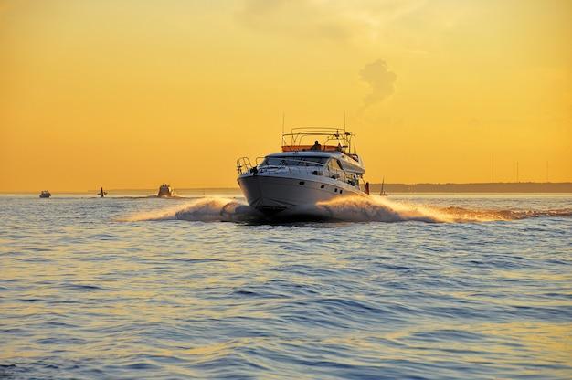 Yachten bei sonnenuntergang in bewegung.
