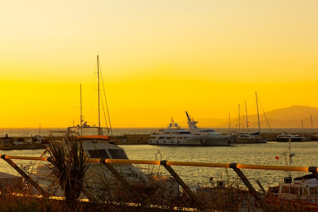 Yachten im seehafen bei sonnenuntergang angedockt. seelandschaft mit booten und berg. marineparkplatz des motorboots