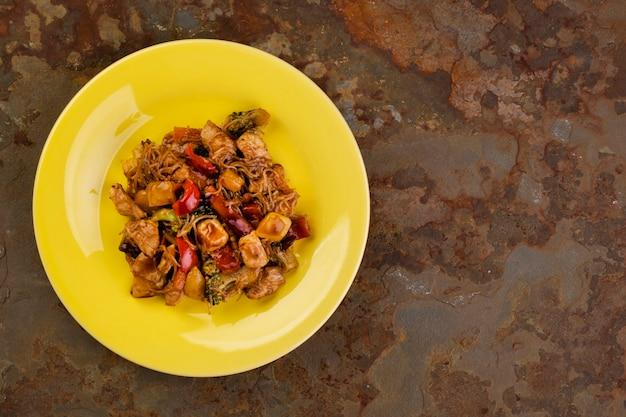 Yakisoba mit hühnerfleisch auf einem gelben teller auf einem rostigen schieferstein - draufsicht