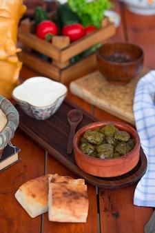 Yarpag dolmasi, yaprak sarmasi, grüne weinblätter gefüllt mit reis und fleisch in töpferschale mit joghurt.