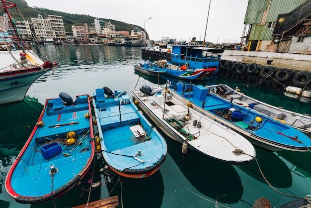 Yehliu fischereihafen mit den fischerbooten, die auf den fluss im fischerdorf in nord-taipeh schwimmen.