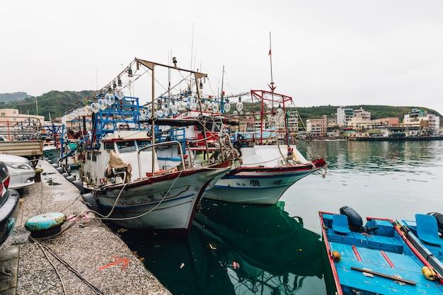 Yehliu fischereihafen mit den fischerbooten, die auf den fluss im fischerdorf schwimmen.