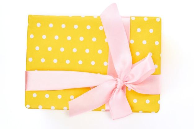 Yello gepunktete geschenkbox, weißer hintergrund.