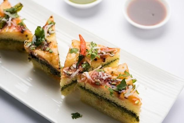Yellow sandwich dhokla ist ein indischer herzhafter snack aus kichererbsenmehl oder reismehl, ursprung in gujarat. serviert mit grünem und tamarinden-chutney. selektiver fokus
