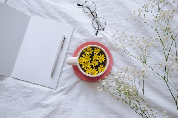 Yellow¡up mit gelben blumen im inneren, auf einem weißen bett mit notizblock und stift.