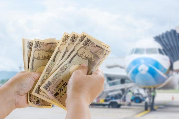 Yen-banknoten in der hand, die zum reise-tourismus auf unscharfem hintergrund bereit sind