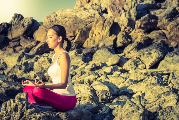 Yoga-aktion der jungen frau am strand