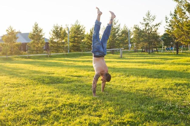 Yoga, fitness und gesunder lebensstil konzept - mann, der einen handstand auf sommerlicher natur tut