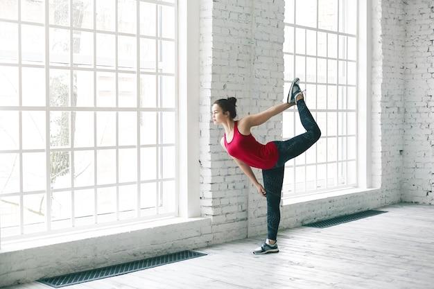 Yoga, flexibilität, energie und kraftkonzept. innenaufnahme des attraktiven brünetten mädchens, das trendiges trägershirt, leggings und laufschuhe trägt, die natarajasana oder lord of dance darstellen