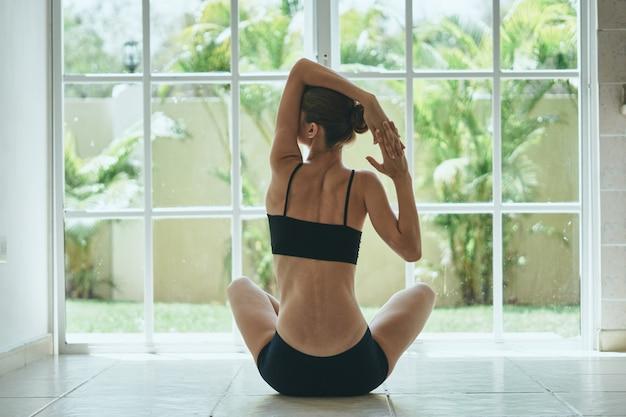 Yoga-frau, die nach hause sport streckt