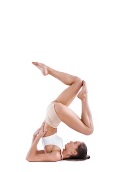 Yoga-frau mit perfektem körper, der yoga praktiziert, wirft in voller länge im studio auf weiß auf. übungen zum ausbalancieren.