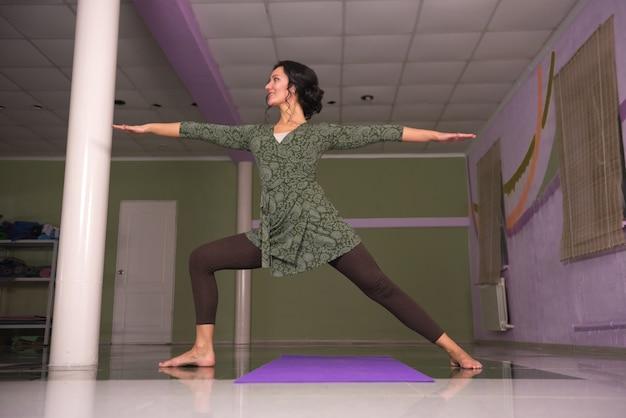 Yoga-frau präsentiert yoga-lassons im fitnesskurs.