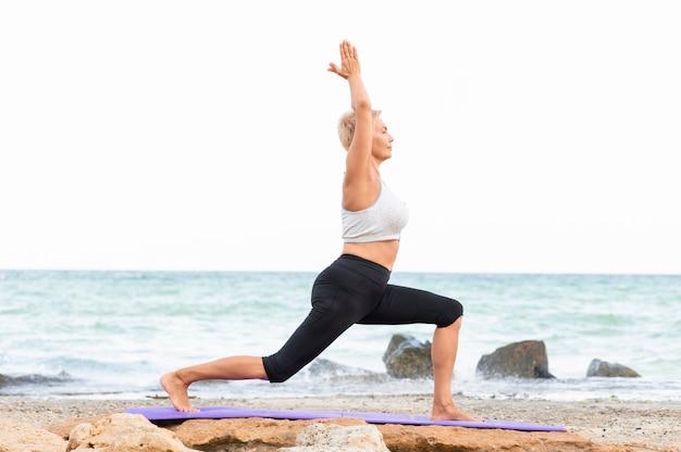 Yoga im freien dehnen. seitenansicht der frau, die yoga praktiziert