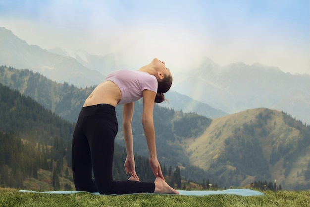 Yoga im freien junge frau, die kamelpose ustrasana asana übung tut